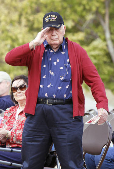 Right: World War II veteran Tom Chesher raises his hand in a salute during the ceremony Satudray. Photos By Paul Hellstern, The Oklahoman