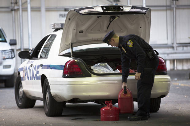 A Federal Reserve officer stocks his vehicle&#039;s trunk with filled fuel containers at the 10th Avenue Hess station, Saturday, Nov. 3, 2012, in New York. Damage wreaked by Superstorm Sandy prevented fuel shipments throughout the metropolitan area for days, leading to shortages and long queues that continue into the weekend. (AP Photo/ John Minchillo) ORG XMIT: NYJM106