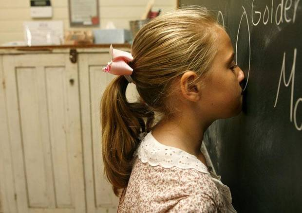 Jacquelyn Renner, 9, places her nose against the chalkboard to experience older forms of student discipline during 1889 School Camp at the 1889 Territory School in Edmond, Okla. Tuesday, July 7, 2009.  Photo by Ashley McKee, The Oklahoman   ORG XMIT: KOD