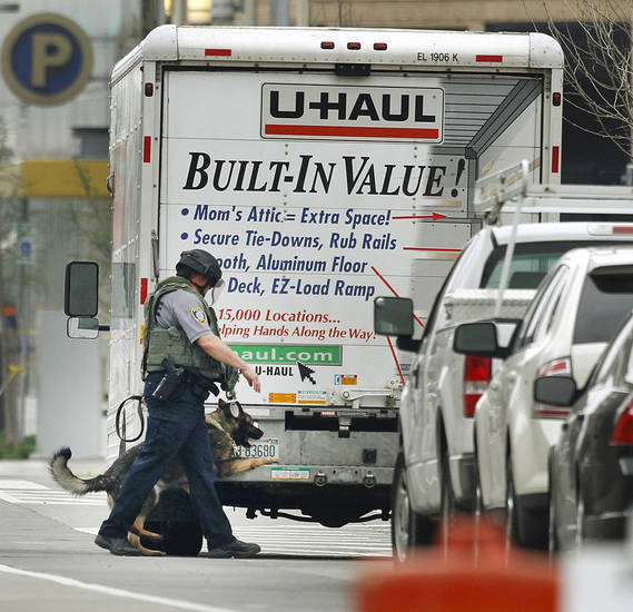 BOMB SCARE: An Oklahoma City K-9 officer checks for explosives as they search a U-Haul truck parked on Walker Avenue in downtown Oklahoma City , Wednesday April 17, 2013. Photo By Steve Gooch, The Oklahoman ORG XMIT: OKC1303121532440650