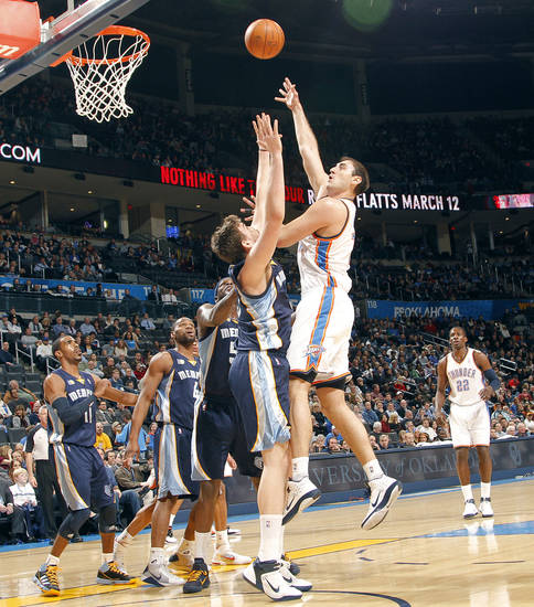 The Thunder's Nenad Krstic (12) puts up a shot over Memphis' Marc Gasol (33) during the NBA basketball game between the Oklahoma City Thunder and the Memphis Grizzlies at the Oklahoma City Arena on Tuesday, Feb. 8, 2011, Oklahoma City, Okla.
