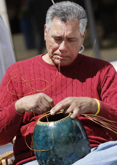Lawton artist John Hernandez weaves pine needle onto a piece of pottery at the Festival of the Arts in downtown Oklahoma City  Wednesday, April 24, 2013. The Hunters are from Piedmont. Photo by Doug Hoke, The Oklahoman
