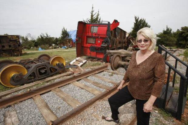 Debbie Morris, owner of The Red Rooster Guest Cabooses and Inn, stands by major damage from the May 24 tornado in Canadian County