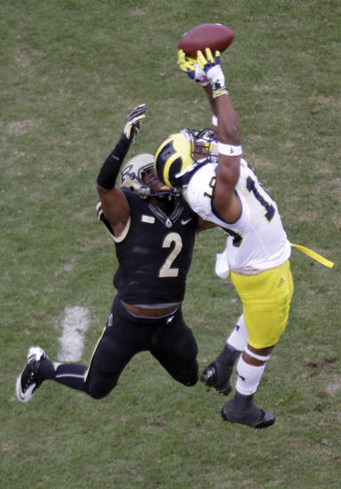 Michigan wide receiver Jeremy Gallon, right, attempts to make a catch over Purdue defensive back Frankie Williams during the second half of an NCAA college football game in West Lafayette, Ind., Saturday, Oct. 6, 2012. Michigan defeated Purdue 44-13. (AP Photo/Michael Conroy)