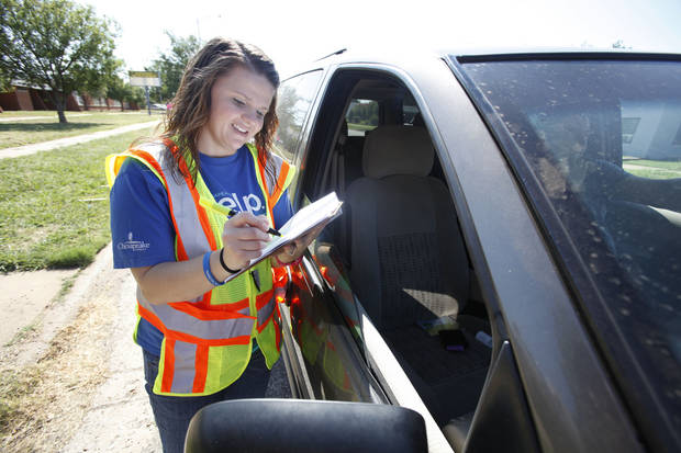 Volunteer Kandy Golden checks a car in Tuesday during a charity drive between Feed The Children and Mustard Seed Development Corporation in Oklahoma City. Photos By Steve Gooch, The Oklahoman