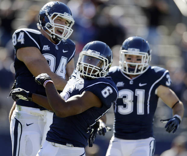 Connecticut wide receiver Michael Smith (6) celebrates his touchdown with teammates tight end Ryan Griffin (94) and wide receiver Nick Williams (31) in the first quarter of an NCAA football game against Temple in East Hartford, Conn., Saturday, Oct. 13, 2012. (AP Photo/Michael Dwyer)