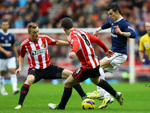 Tottenham Hotspur's Gareth Bale, right, vies for the ball with Sunderland's Craig Gardner, center, and Sebastian Larsson, left, during their English Premier League soccer match at the Stadium of Light, Sunderland, England, Saturday Dec. 29, 2012. (AP Photo/Scott Heppell)