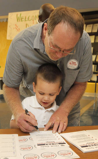 Frank Fowler helps his stepson Lazzen Hendricks, 4, sign the pledge during Take Your Child to School Day at Martin Luther King Elementary School, Friday, September 21, 2001.   Six Oklahoma City Public Schools will be part of the inaugural event. Photo By David McDaniel/The Oklahoman