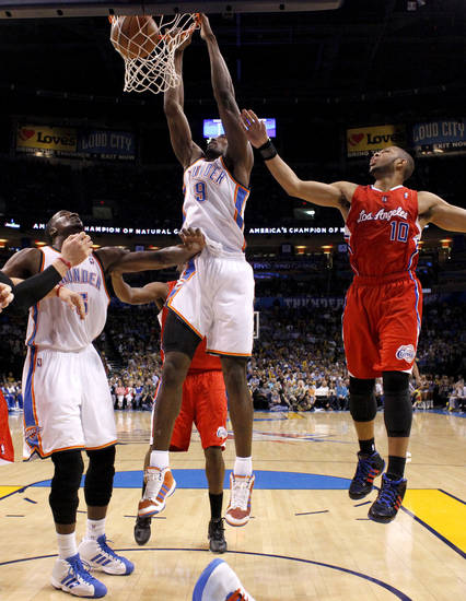 Oklahoma City's Serge Ibaka (9) dunks the ball beside Kendrick Perkins (5) and Los Angeles Clippers' Eric Gordon (10) during the NBA basketball game between the Oklahoma City Thunder and the Los Angeles at the Oklahoma City Arena, Wednesday, April 6, 2011. Photo by Bryan Terry, The Oklahoman