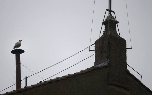A seagull sits on the chimney on the roof of the Sistine Chapel, in St. Peter's Square during the second day of the conclave to elect a new pope at the Vatican, Wednesday, March 13, 2013. (AP Photo/Gregorio Borgia) ORG XMIT: VAT117