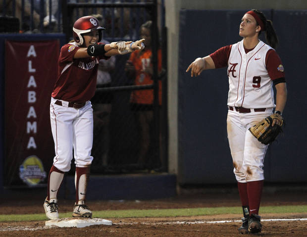 Oklahoma's Brianna Turang (2) celebrates after sliding into third base past Alabama's Courtney Conley (9) during a Women's College World Series game between OU and Alabama at ASA Hall of Fame Stadium in Oklahoma City, Monday, June 4, 2012.  Photo by Garett Fisbeck, The Oklahoman