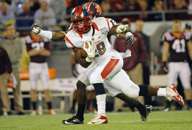 Rutgers running back Savon Huggins (28) runs for a gain of 11 yards in front of Virginia Tech&#039;s Detrick Bonner during the first quarter of an NCAA college football Russell Athletic Bowl game on Friday, Dec. 28, 2012, in Orlando, Fla. (AP Photo/Brian Blanco)