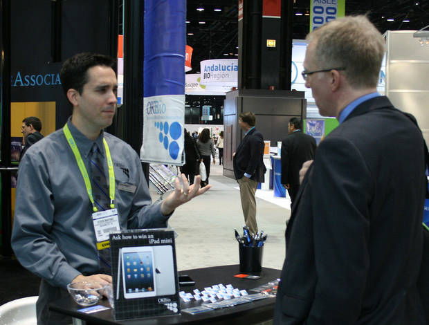 Steven Martinez, who works at the Oklahoma Center for the Advancement of Science and Technology, greets visitors Wednesday at the OKBio booth. <strong>unknown - JIM STAFFORD</strong>