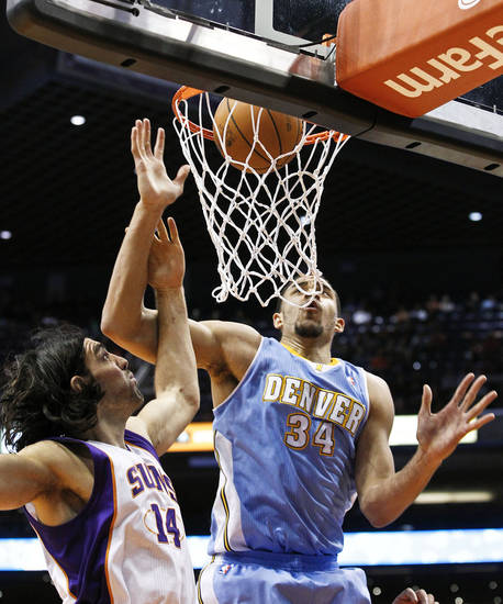 Phoenix Suns' Luis Scola (14), of Argentina, and Denver Nuggets' JaVale McGee (34) watch as the ball goes through the net for a score in the first half of an NBA basketball game, Monday, Nov. 12, 2012, in Phoenix. (AP Photo/Ross D. Franklin)
