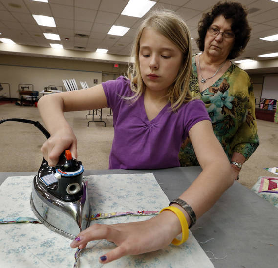 Gracie Skelton, 11, irons quilt pieces while her aunt, Vicki Borycki, watches during a quilting demonstration Saturday at the Norman Public Library. PHOTOS BY STEVE SISNEY, THE OKLAHOMAN