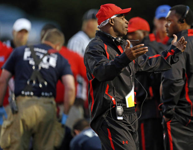 Coach Deion Sanders motions for his players to join around injured Millwood player Andre Clanton (22) before signaling Millwood players, too, while emergency medical workers check on Clanton during a high school football game between Millwood and Prime Prep Academy in Oklahoma City, Friday, Sept. 14, 2012. Clanton was taken from the game in an ambulance. Photo by Nate Billings, The Oklahoman