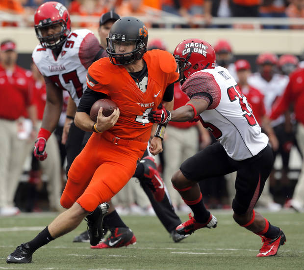 Oklahoma State's J.W. Walsh (4) rushes as Louisiana-Lafayette's Trevence Patt (33) tries to tackle him during a college football game between Oklahoma State University (OSU) and the University of Louisiana-Lafayette (ULL) at Boone Pickens Stadium in Stillwater, Okla., Saturday, Sept. 15, 2012. Photo by Sarah Phipps, The Oklahoman