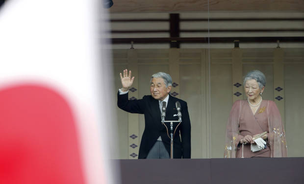 Japan's Emperor Akihito waves to a crowd of well-wishers with his wife Empress Michiko during a morning appearance through the bulletproof glass of a balcony to mark his 79th birthday,  at Imperial Palace in Tokyo Sunday, Dec. 23, 2012.  (AP Photo/Shizuo Kambayashi)