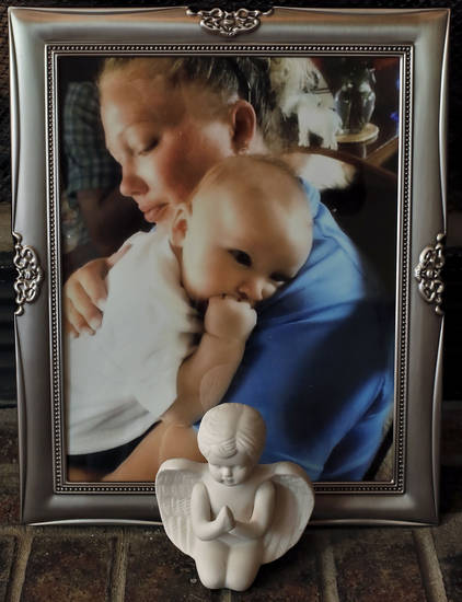A photo of Megan Futrell holding her son Case sits in the family's living room in south Oklahoma City. Futrell and her infant son Case were killed by the May 20 tornado that hit the 7-Eleven in Moore where they sought shelter. <strong>CHRIS LANDSBERGER - CHRIS LANDSBERGER</strong>