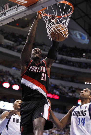 Portland Trail Blazers' J.J. Hickson (21) dunks over Dallas Mavericks' Shawn Marion, left bottom, and Brandan Wright (34) in the first half of an NBA basketball game, Monday, Nov. 5, 2012, in Dallas. (AP Photo/Tony Gutierrez)