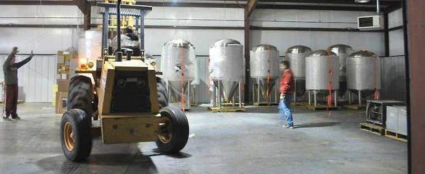 Workers move brewing equipment into Roughtail Brewing Co.�s brewhouse in Midwest City. The brewery moved its headquarters to Midwest City from Oklahoma City and now is using an online funding campaign to raise money for an automated canning line. Roughtail is one of two local breweries using the online tool. PHOTO PROVIDED BY ROUGHTAIL BREWING CO.