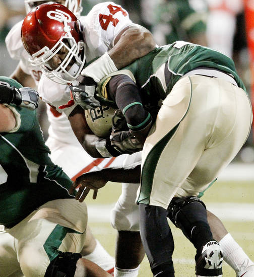 Jeremy Beal (44) stops Robert Griffin III (10) during the first half of the college football game between the University of Oklahoma Sooners (OU) and the Baylor Bears (BU) at Floyd Casey Stadium on Saturday, November 20, 2010, in Waco, Texas.   Photo by Steve Sisney, The Oklahoman