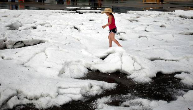 Riley Thompson, 8, of Edmond, Okla., plays on mound of hail stones in the Sam's Club parking lot on Penn Avenue near Memorial Road, Sunday, May 16, 2010 in Oklahoma City. Photo by Sarah Phipps, The Oklahoman