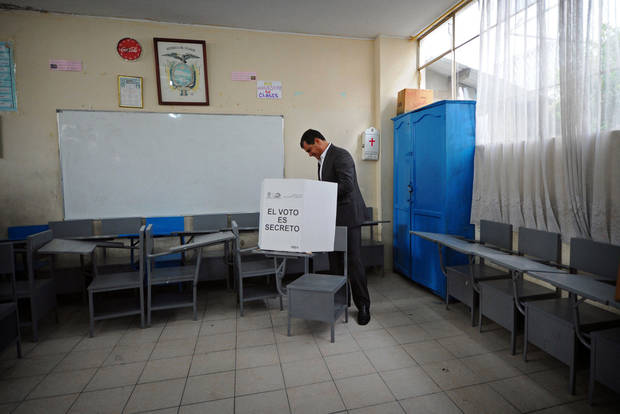 President Rafael Correa votes at a polling station in Quito, Ecuador, Sunday, Feb. 17, 2013.  Ecuadoreans  elect president,  vice-president and National Assembly members Sunday with Correa highly favored to win a second re-election.(AP Photo/Dolores Ochoa)