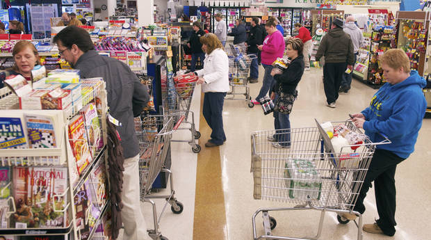 Shoppers line-up to check out at the Sureway Eastgate, in Henderson, Ky., as people stock up on essentials before the forecasted blizzard late Christmas evening, Tuesday, Dec. 25, 2012. (AP Photo/The Gleaner, Mike Lawrence)