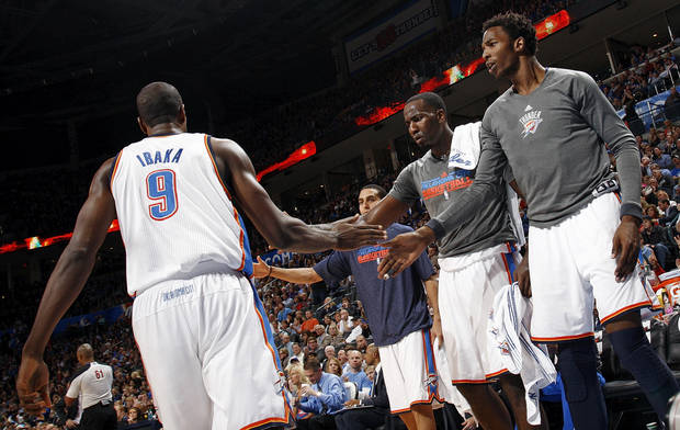 Oklahoma City's Hasheem Thabeet (34), Kendrick Perkins (5) and Kevin Martin (23) celebrate with Serge Ibaka (9) after a play during an NBA basketball game between the Oklahoma City Thunder and the San Antonio Spurs in Oklahoma City Monday, Dec. 17, 2012. Oklahoma City won, 107-93. Photo by Nate Billings, The Oklahoman