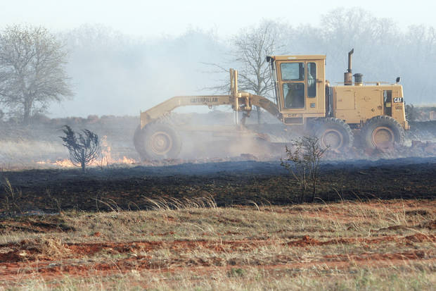 A grader driver tries to stop wildfires that destroyed several structures Thursday in Lindsay.  Photo by Steve Sisney, The Oklahoman