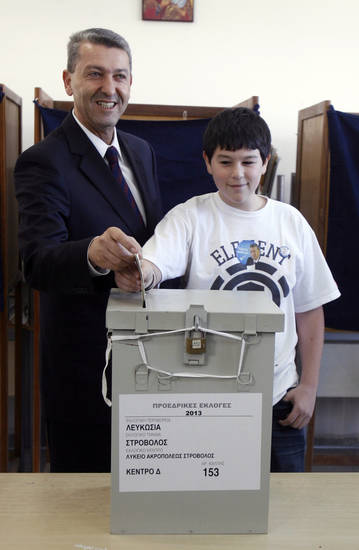 Presidential candidate Giorgos Lillikas and his son Orfeas vote in the Presidential election in capital Nicosia, Cyprus, Sunday, Feb. 17, 2013. Cypriots are voting for a new president amid a financial crisis in which the country needs a rescue package from international creditors to stave off bankruptcy. (AP Photo/Philippos Christou)