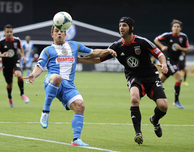 Philadelphia Union midfielder Danny Cruz, left, battles for the ball against D.C. United defender Daniel Woolard, right, during the first half of an MLS soccer match, Sunday, April 21, 2013, in Washington. (AP Photo/Nick Wass)