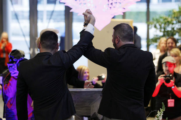 Newlyweds Corianton Hale, left, and Keith Bacon raise their arms in celebration after marrying at Seattle City Hall, Sunday, Dec. 9, 2012, in Seattle. Gov. Chris Gregoire signed a voter-approved law legalizing gay marriage Wednesday, Dec. 5 and weddings for gay and lesbian couples began in Washington on Sunday, following the three-day waiting period after marriage licenses were issued earlier in the week. (AP Photo/Elaine Thompson)