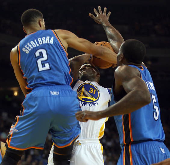 The Golden State Warriors' Festus Ezeli (31) is double teamed by the Oklahoma City Thunder's Thabo Sefolosha (2) and Kendrick Perkins (5) at Oracle Arena in Oakland, California, on Wednesday, January 23, 2013. (Jane Tyska/Oakland Tribune/MCT) ORG XMIT: 1134056
