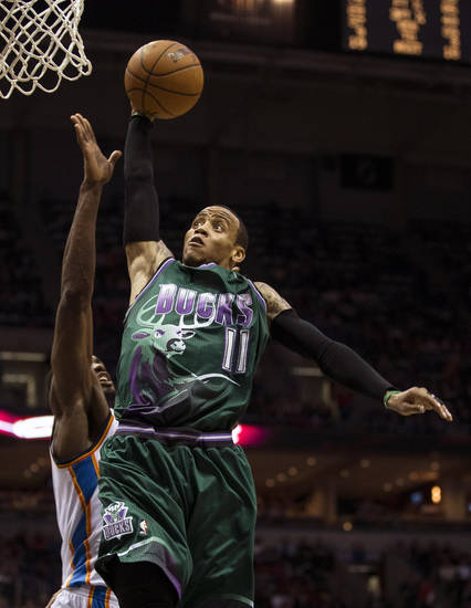 Milwaukee Bucks' Monta Ellis (11) goes in for a dunk past Oklahoma City Thunder's Serge Ibaka during the second half of an NBA basketball game on Saturday, March 30, 2013, in Milwaukee. (AP Photo/Tom Lynn)