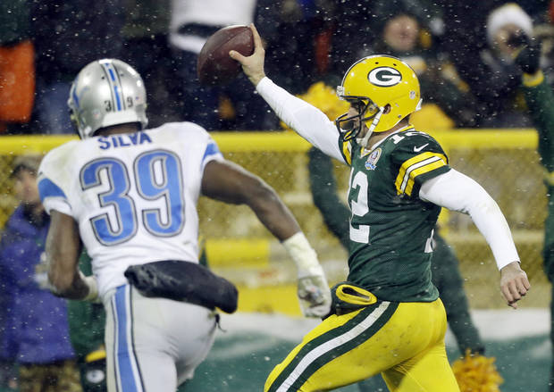 Green Bay Packers quarterback Aaron Rodgers breaks away from Detroit Lions' Ricardo Silva (39) for a 27-yard touchdown run during the second half of an NFL football game Sunday, Dec. 9, 2012, in Green Bay, Wis. (AP Photo/Jeffrey Phelps)