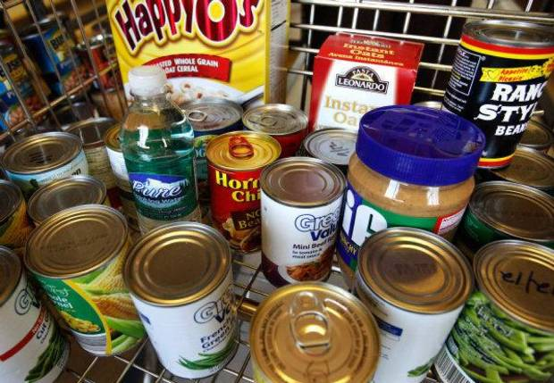 Food sits in a shopping cart after it was pulled from shelves  in the food pantry at Putnam City West High School. Students battling hunger can take items from the food pantry twice a month.  <strong>JIM BECKEL - THE OKLAHOMAN</strong>