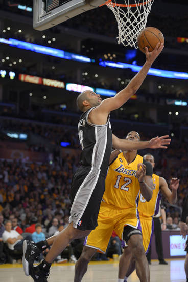 San Antonio Spurs guard Cory Joseph, left, goes to the basket past Los Angeles Lakers center Dwight Howard during the first half in Game 3 of a first-round NBA basketball playoff series, Friday, April 26, 2013, in Los Angeles. (AP Photo/Mark J. Terrill)