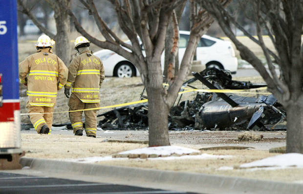 Oklahoma City firefighters walk past the wreckage of a medical helicopter, which crashed Friday between a nursing home and retirement center in Oklahoma City. Two people were killed in the crash, and another was critically injured. Photo By Paul Hellstern