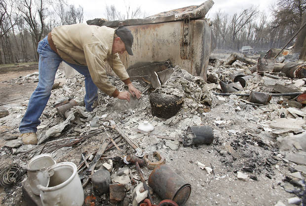 Kenneth Wertz dig through the remains of his house of more than 40 years as he looks for a few salvageable remains from the house that was destroyed by wildfires on Friday, April 10, 2009, in Choctaw, Okla.  Photo by Chris Landsberger, The Oklahoman