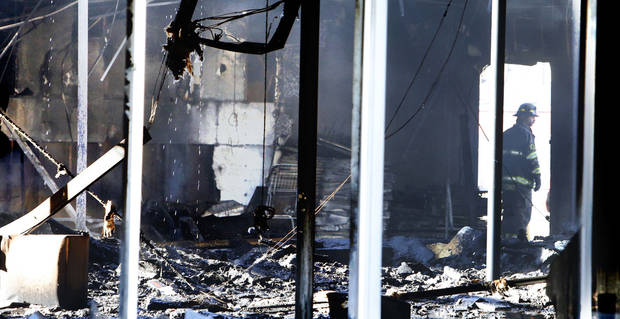 A firefighter works Thursday inside a burned building at 400 E Main in Tuttle. Photos by Steve Sisney, The Oklahoman