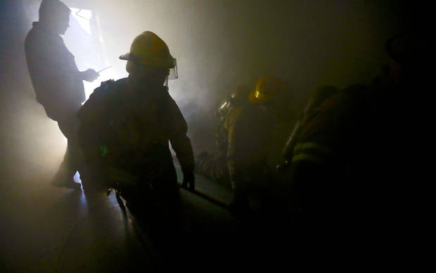 Edmond firefighters make their way through a smoke-filled building in downtown as part of a self-contained breathing apparatus drill. PHOTO BY CHRIS LANDSBERGER, THE OKLAHOMAN. &lt;strong&gt;CHRIS LANDSBERGER - THE OKLAHOMAN&lt;/strong&gt;