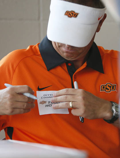 OSU offensive coordinator Todd Monken puts on his name tag before meeting fans during OSU Fan Appreciation Day at Gallagher-Iba Arena in Stillwater, Okla., Saturday, Aug. 4, 2012. Photo by Nate Billings, The Oklahoman