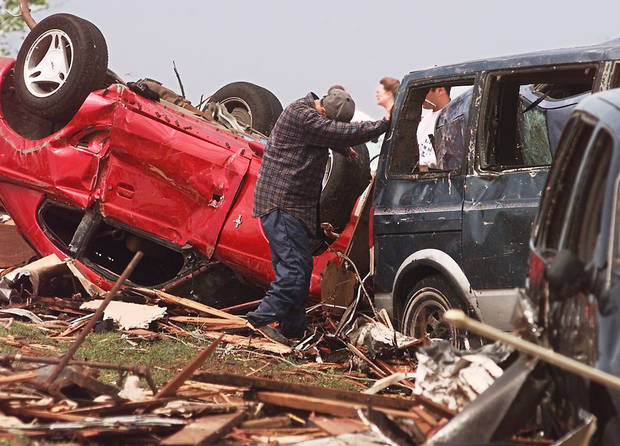 MAY 3, 1999 TORNADO: Tornado damage, victims: David Mahan, 14, drops his head as he leans against a damaged van across the street from his grandmother's house in Midwest City.  The overturned red car is Mahan's father's car.