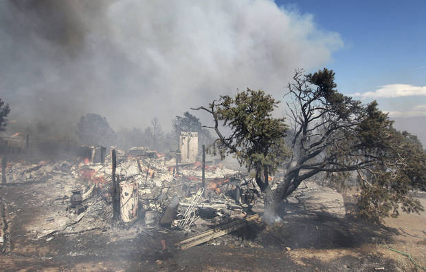 What remains of a building in Topaz Ranch Estates smolders as firefighters battle a wind-driven fire that has destroyed at least two homes and a number of outbuildings south of Gardnerville, Nev., on Tuesday, May 22, 2012. (AP Photo/Cathleen Allison)