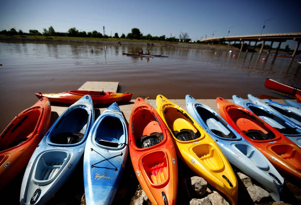 Competitors paddle pass boats lend up on the shore line during races for the USA Canoe/Kayak World Cup Team Trials on the Oklahoma River,  Saturday, April 21, 2012. Photo by Sarah Phipps, The Oklahoma