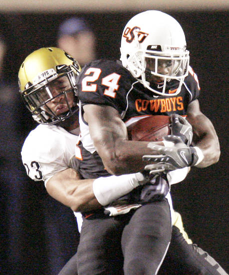 OSU's Kendall Hunter, right, is brought down by Colorado's Jalil Brown during the Cowboys' win in Stillwater on Nov. 19. Photo by Bryan Terry, The Oklahoman
