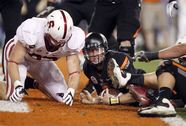 Oklahoma State quarterback Brandon Weeden, right, looks up for the touchdown signal from the official after rushing for a touchdown in front of Stanford linebacker Terence Murphy, left, during the first half of the Fiesta Bowl NCAA college football game Monday, Jan. 2, 2012, in Glendale, Ariz. (AP Photo/Paul Connors)