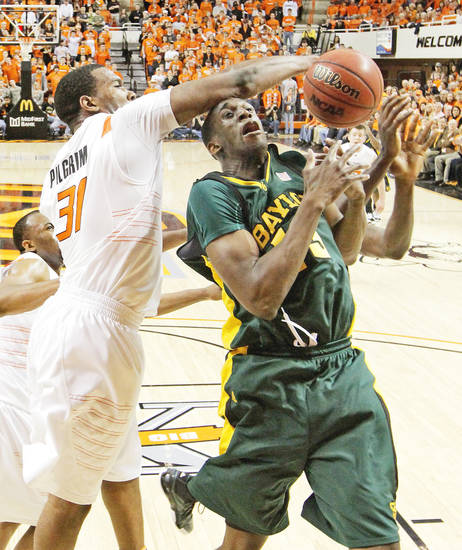 Oklahoma State's Matt Pilgrim, left, blocks a shot by Udoh during Saturday's game.